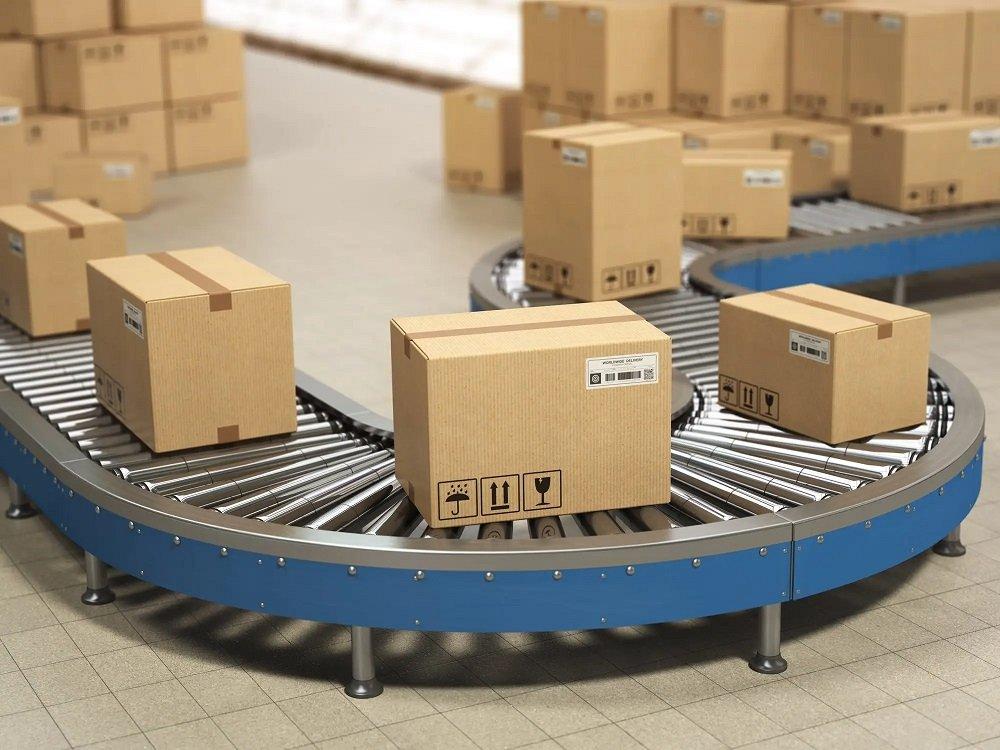 Cardboard boxes on conveyor roller in distribution warehouse, De